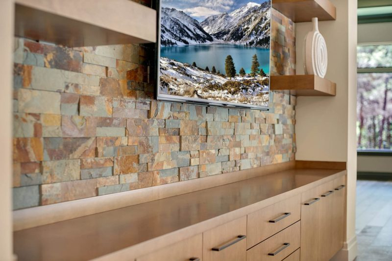 custom stone wall with wood shelves and wooden cabinets