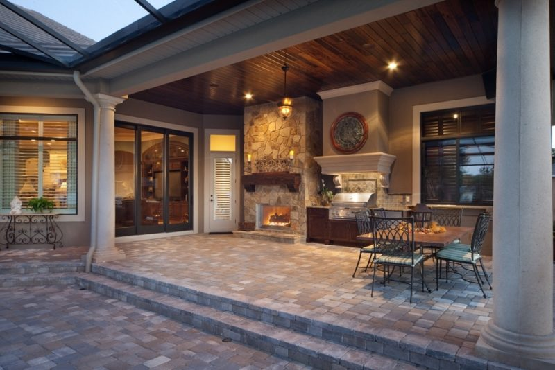 custom outdoor patio kitchen with stone fireplace