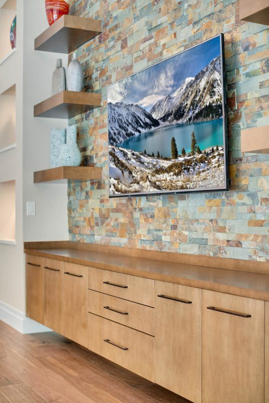 Custom stone wall with wood shelving and counter